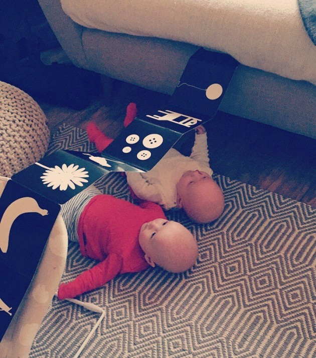Baby twins underneath baby book. Baby entertainment